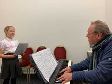 Singing teacher Mr Chris working with one of his students at the keyboard